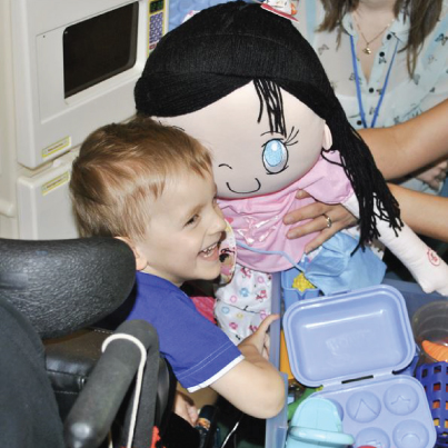 A little boy in Shriners Hospital boy being gifted with My Friend Huggles Bia