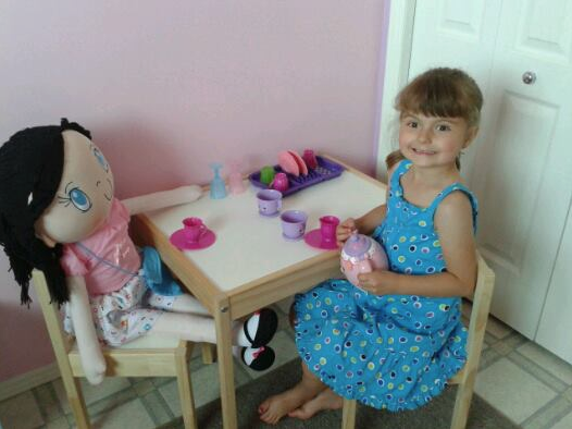 Cute photo of a little girl playing tea party with her My Friend Huggles doll