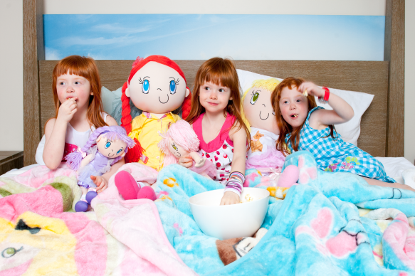Adorable photo of triplets having a sleepover party with My Friend Huggles dolls